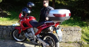 Motorcyclist near a red motorbike during his trip
