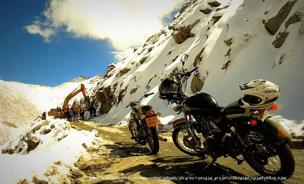 two parked motorcycles in snowy mountines